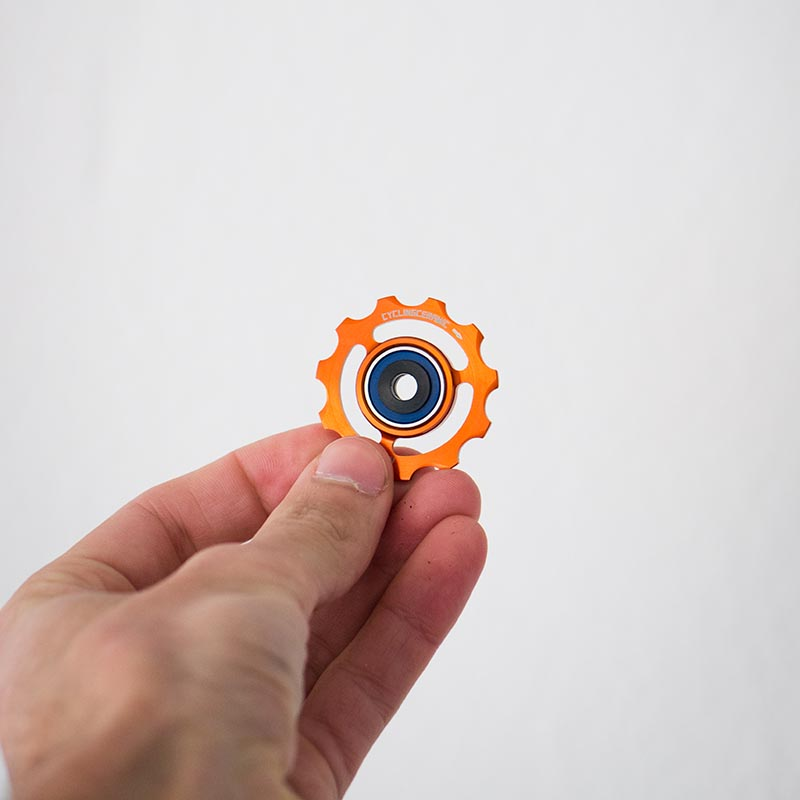 An orange anodized jockey wheels handled in hand